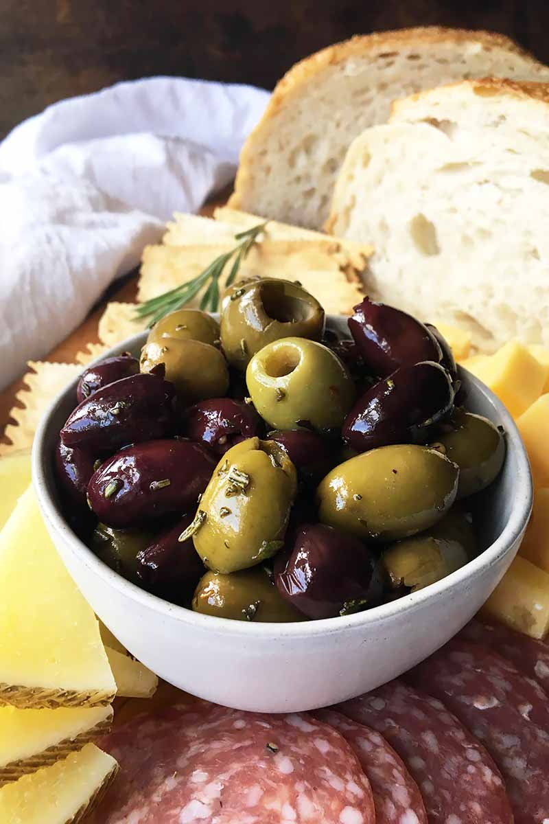 Vertical image of a bowl of olives next to bread, cheese, and sliced meats.