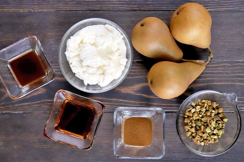 Horizontal overhead image of three small square glass dishes of vanilla, maple syrup, and ground cinnamon, and small round glass bowls of ricotta and chopped pistachios, with three brown Bosc pears on a dark brown wood surface.