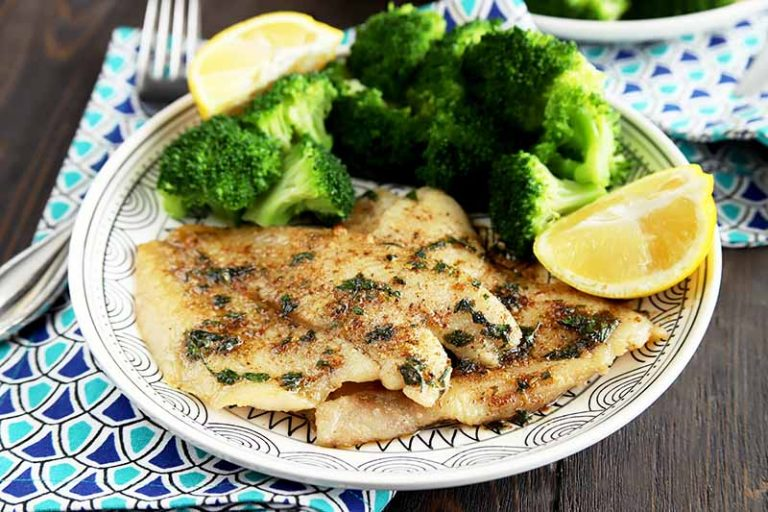 Horizontal image of a plate with cooked sole with herbs on a plate with broccoli and lemons, with a blue napkin and fork.