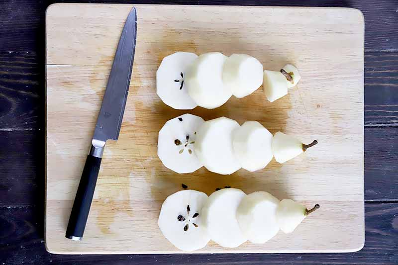 Horizontal image of a knife and sliced peeled pear on a cutting board.