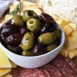 Horizontal image of a white bowl with olives on a cheese and charcuterie board.