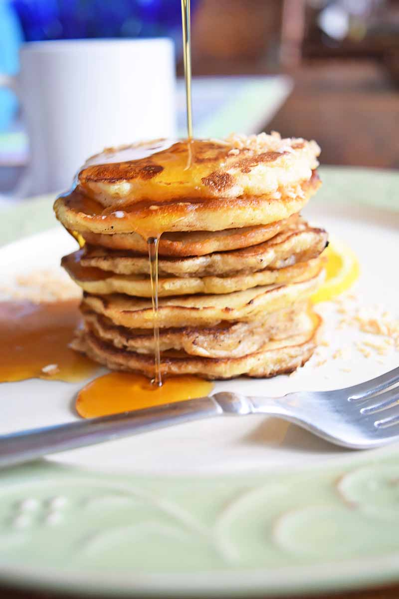 Vertical image of a tall stack of pancakes with syrup being poured over them on a plate with a fork.