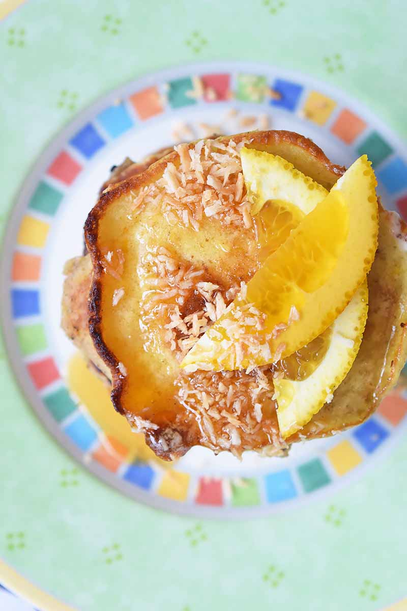 Vertical top-down image of pancakes with browned, crispy edges with garnishes of syrup, orange slices, and white flakes.