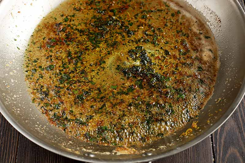 Horizontal image of brown butter with fresh herbs.