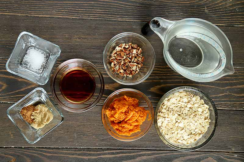 Horizontal image of assorted ingredients in glass dishes on a wooden board.