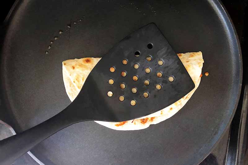 Horizontal overhead image of a plastic spatula pressing down a tortilla that has been folded in half, in a nonstick frying pan coated with a thin layer of oil.
