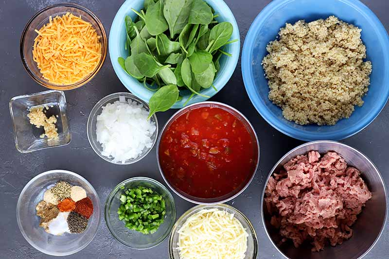 Horizontal image of assorted vegetables, spices, cooked quinoa, cheese, and raw meat in bowls.