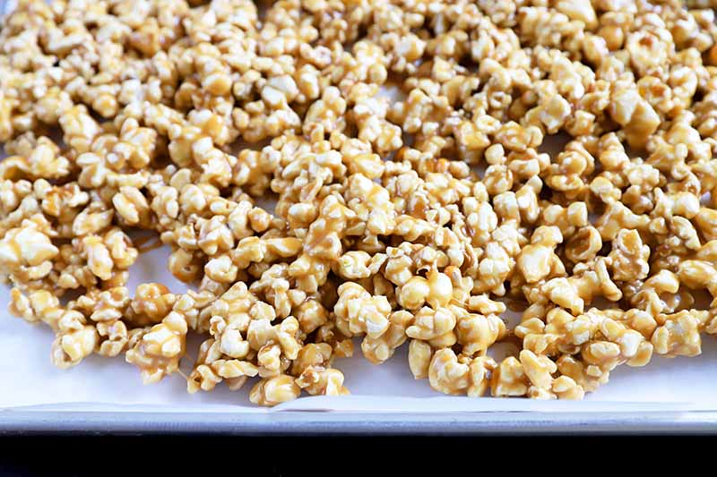 Horizontal image of caramel coated popcorn on a baking sheet lined with parchment paper.
