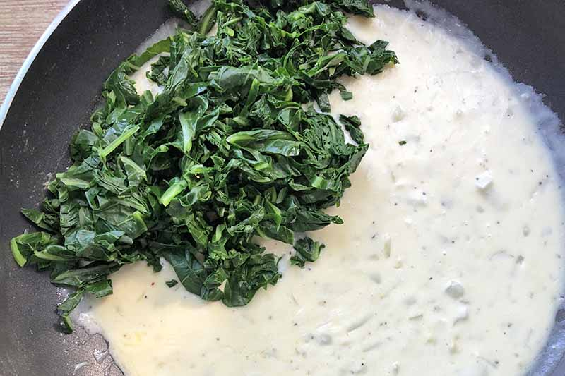 Overhead closely cropped closeup horizontal image of a pile of cooked greens to the left side in a nonstick frying pan of cream sauce, on a wood surface.