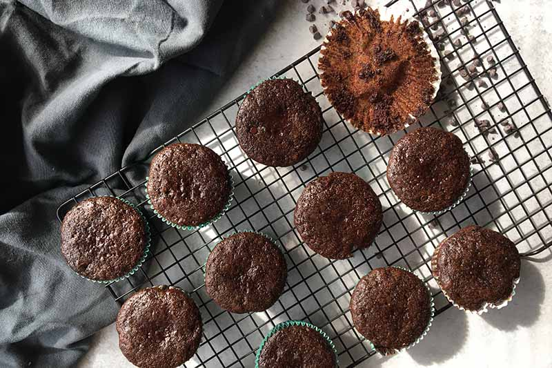 Horizontal image of baked mini dark brown treats on a cooling rack, with one messy liner on the side.