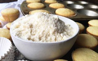 Horizontal image of a small bowl filled with a light white crumbly powder next to mini cupcakes.