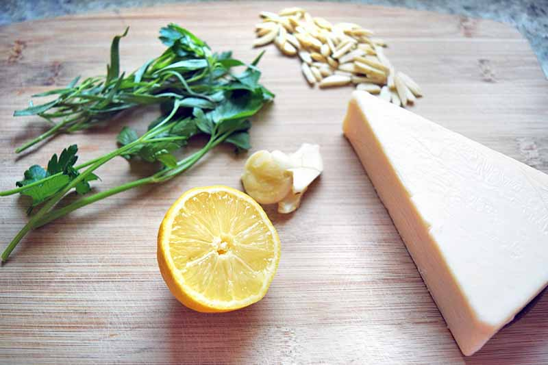 Horizontal oblique overhead image of a block of pecorino cheese, half of a lemon, smashed cloves of garlic, sprigs of fresh flat leaf Italian parsley and tarragon, and slivered almonds, on an unfinished blonde wood cutting board on a top of a gray speckled countertop.