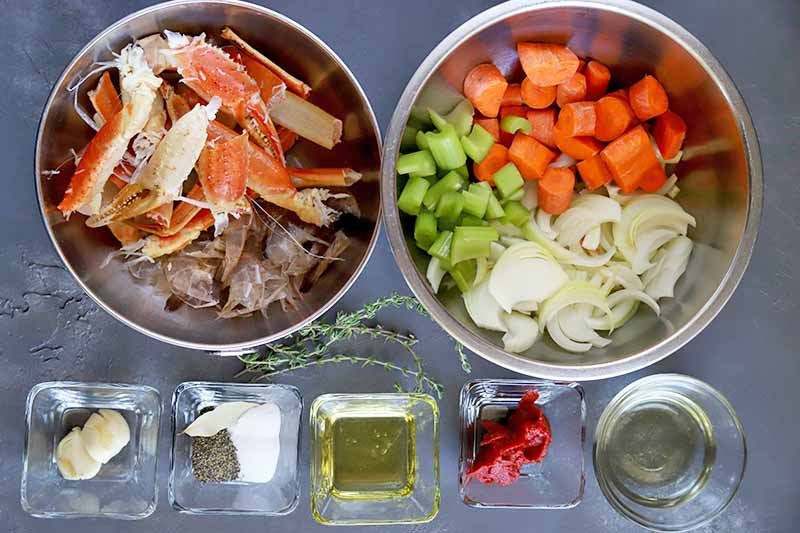 Horizontal top-down image of ingredients in bowls to make seafood stock.