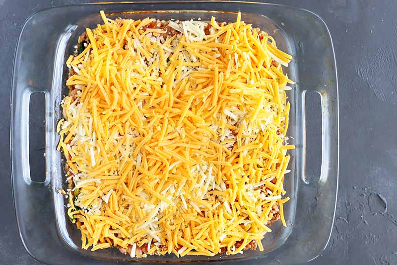 Horizontal image of a glass dish with an unbaked, cheese-topped recipe.