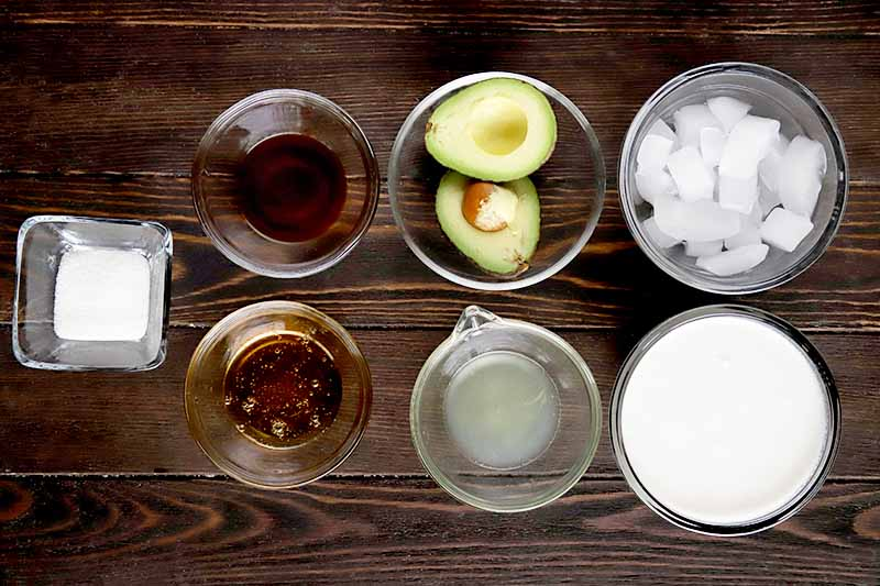 Overhead horizontal image of four small round glass bowls of vanilla, honey, avocado, lime juice, ice, and coconut water, and a small square glass bowl of hydrolyzed collagen powder, on a dark brown wood surface.