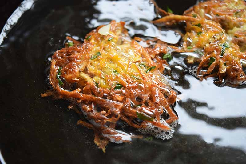 Oblique overhead image of two crispy brown latkes frying in oil in a large cast iron pan.