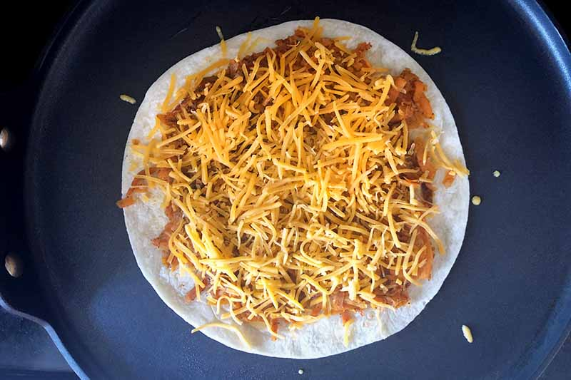 Horizontal overhead image of a flour tortilla topped with a spiced sweet potato mixture and shredded yellow cheddar cheese, in a nonstick frying pan.