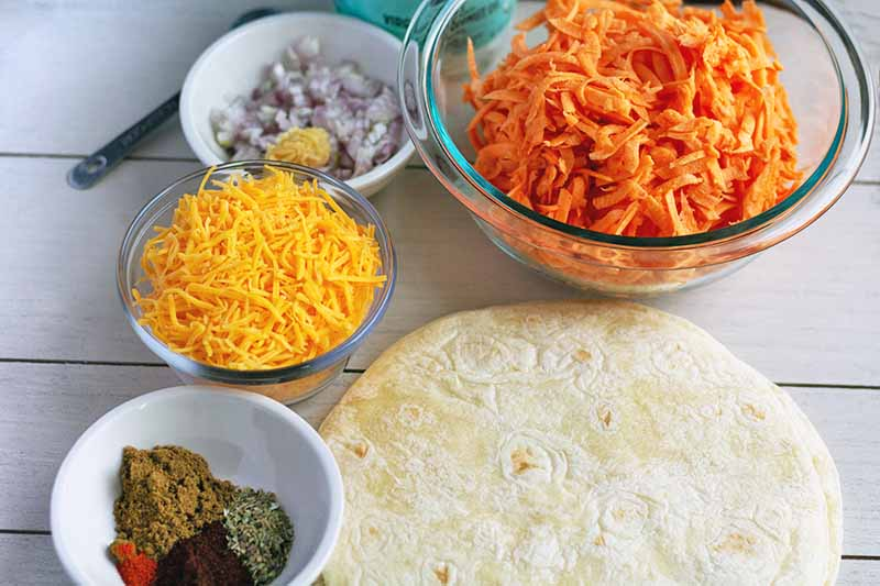 Horizontal oblique overhead image of a glass bowl of shredded sweet potato with smaller porcelain bowls of diced onion, shredded cheese, and various spices, on a white wood surface with a metal measuring spoon at the top left and several flour tortillas at the bottom right of the frame.