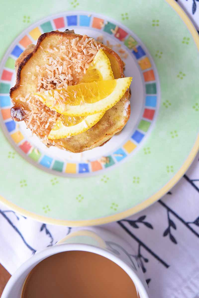 Vertical top-down image of flapjacks with coconut flakes and orange slices next to a cup of coffee.