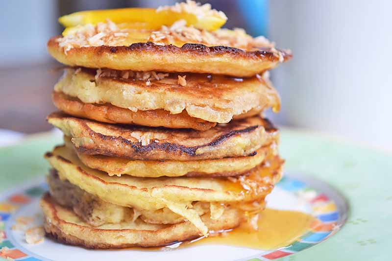 Horizontal image of a stall stack of pancakes on a colorful plate with syrup, orange slices, and coconut flakes.