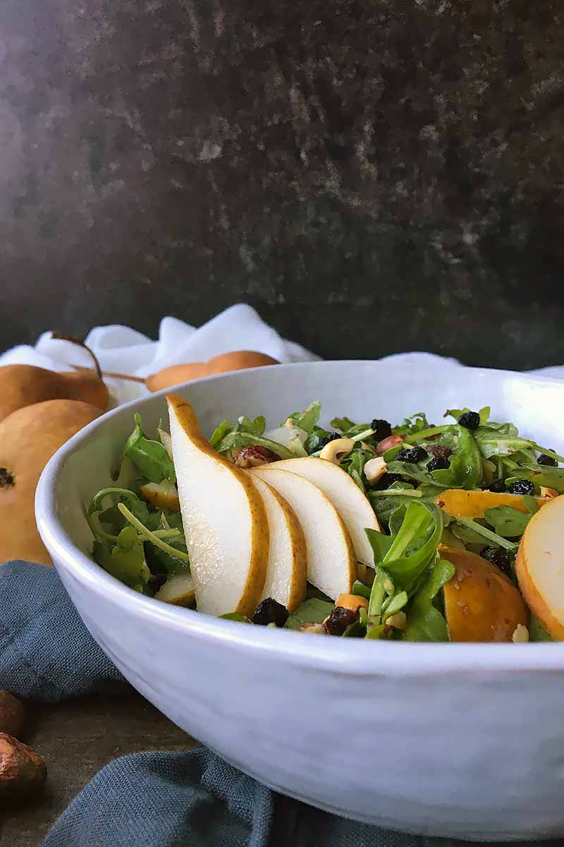 Vertical image of a white bowl with arugula and sliced fresh fruit.