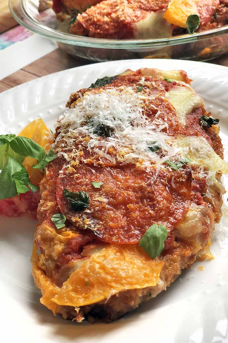 Vertical image of chicken parmesan with pepperoni on a white plate, topped with grated cheese, beside slices of red and yellow tomato and a sprig of fresh basil, with more of the dish in a glass pie plate in the background.