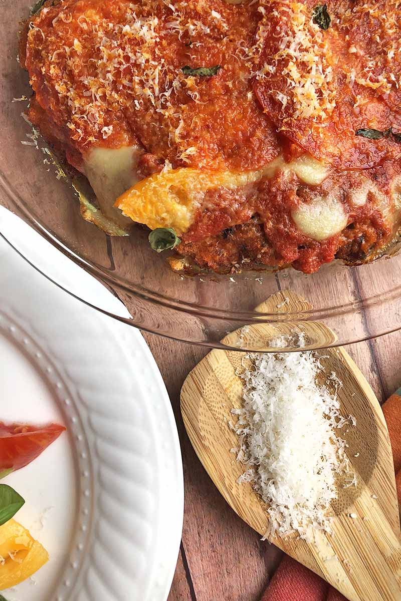 Vertical overhead image of chicken parmesan in a glass pie dish beside a white plate with slices of red and yellow tomato and a sprig of basil on it, on a wood surface with a wooden spoon filled with grated parmesan cheese and a red cloth.