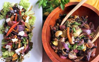 Horizontal overhead image of a white platter at the left and a wooden bowl at the right, filled with roasted vegetable and fresh herb salad, with a set of wooden tongs and sprig of fresh parsley.
