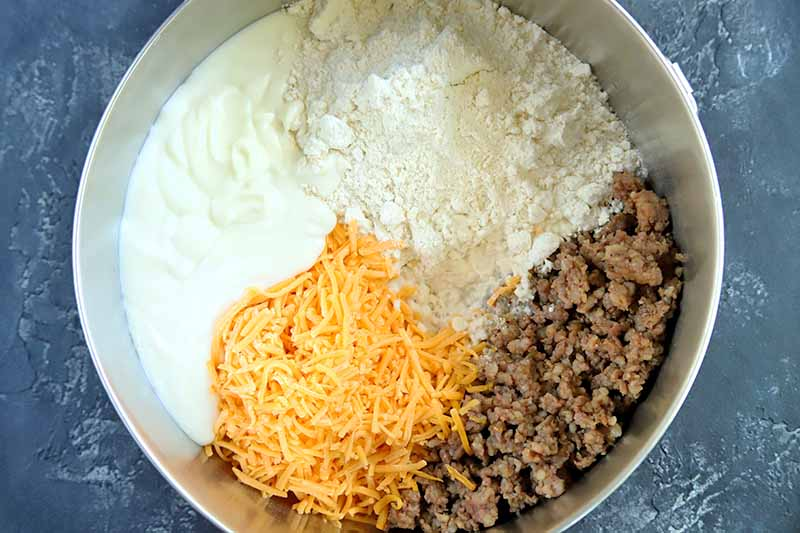 Horizontal overhead image of a large stainless steel bowl with separate portions of mornay sauce, baking mix, crumbled cooked sausage, and shredded orange cheddar cheese at the bottom, ready to be mixed together, on a blue-gray surface.