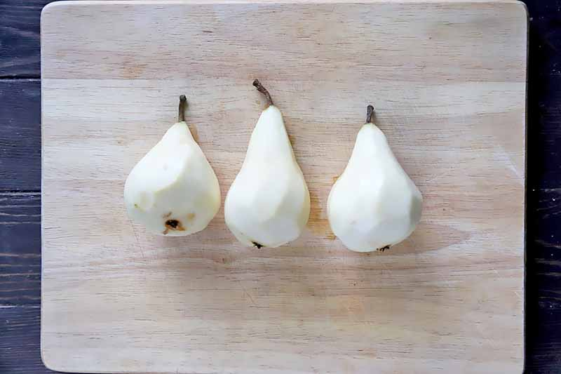 Horizontal image of three whole peeled pears on a wooden cutting board.