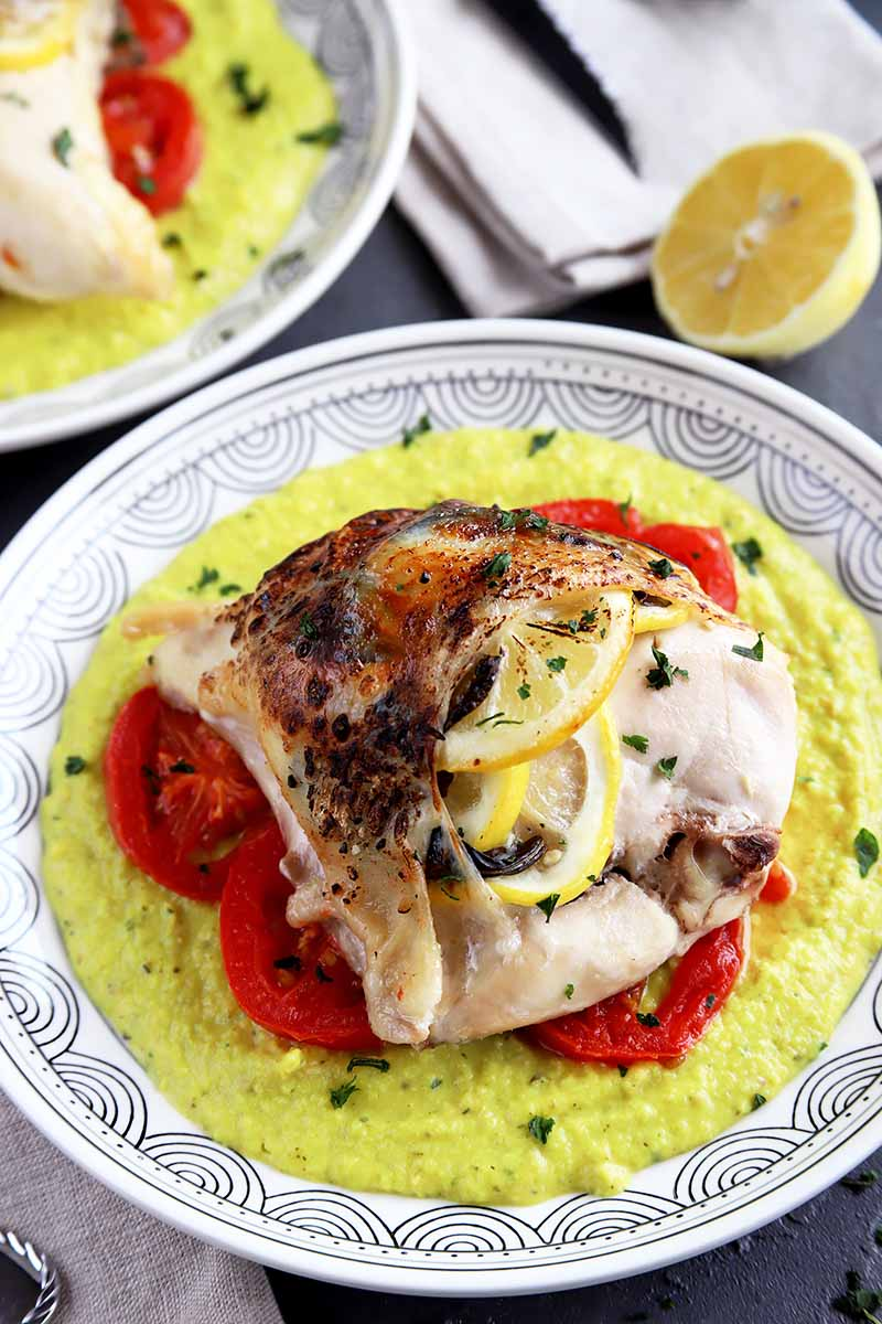 Vertical image of a plate with a thick yellow sauce and sliced tomatoes topped with baked seasoned chicken stuffed with lemon slices.