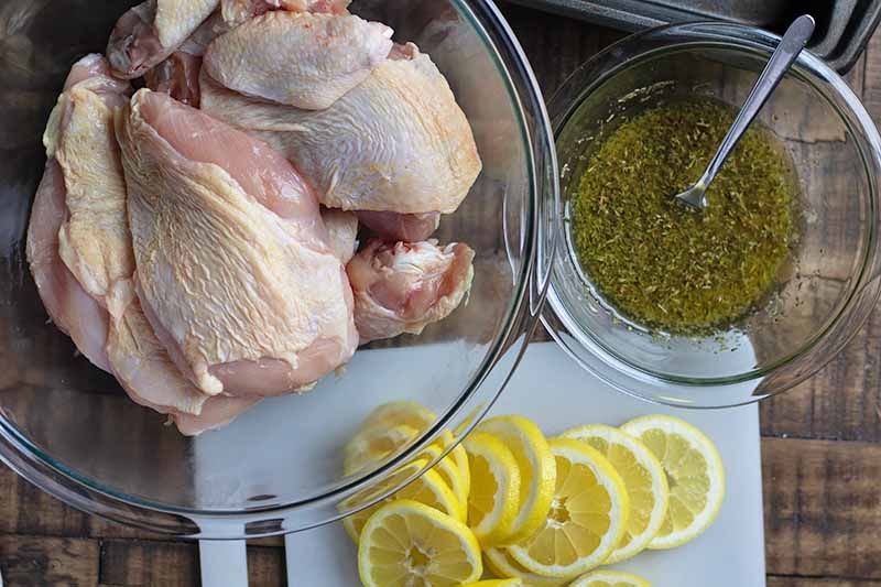 Horizontal image of raw chicken pieces, slices of lemon, and an herb marinade in bowls.