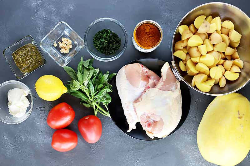 Horizontal image of assorted fresh ingredients, raw poultry, and seasonings in plates and bowls on a gray table.