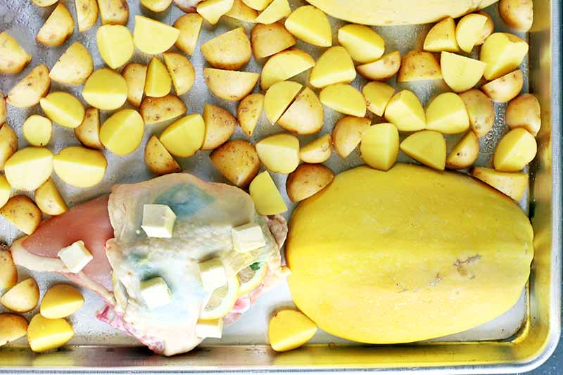 Horizontal image of a baking sheet with sliced tomatoes, cubed potatoes, raw chicken, and a halved yellow spaghetti squash arranged cut side down, with cubes of butter on top of the poultry.