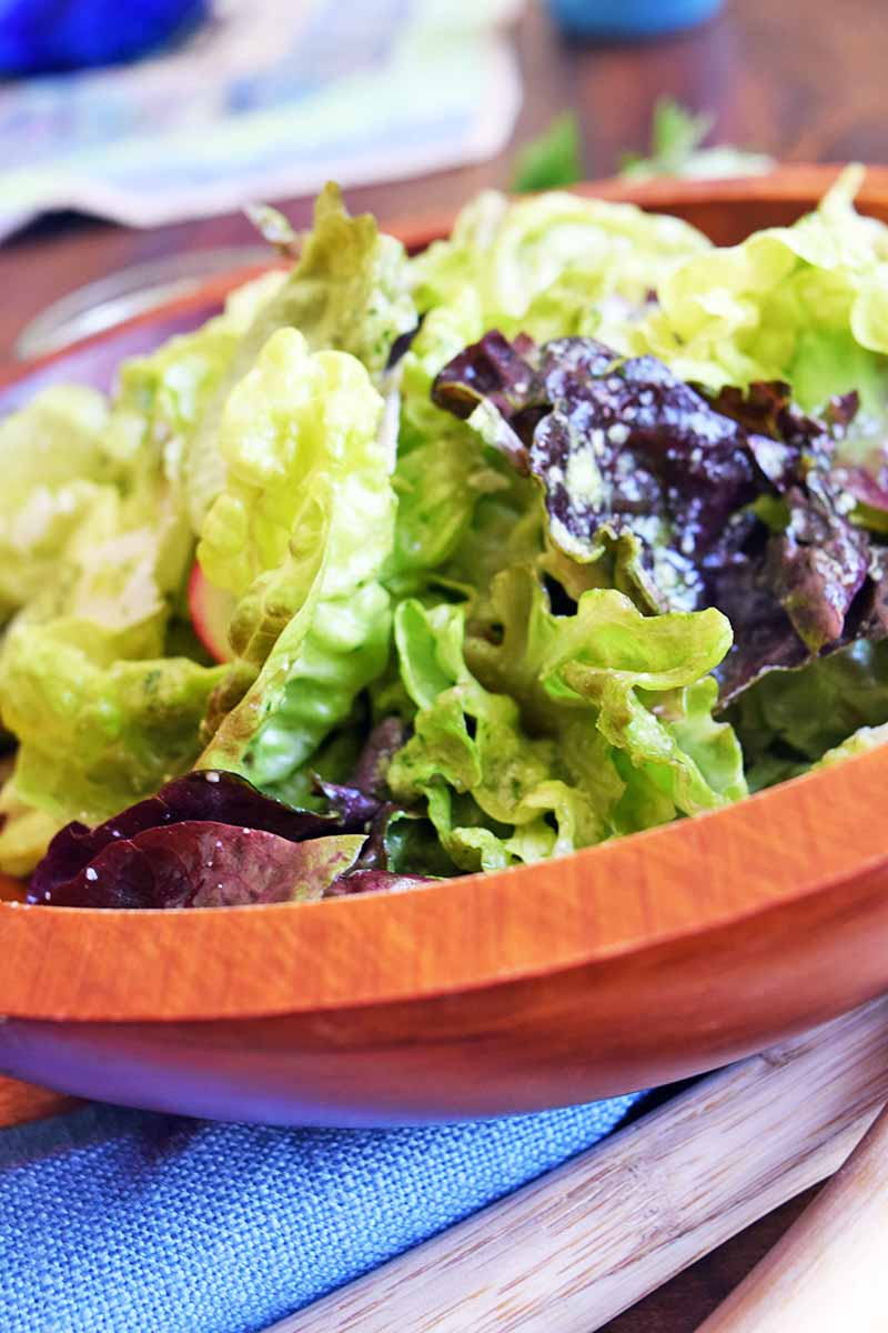 Vertical closely cropped image of a wooden bowl filled with dressed salad greens, on a wood surface topped with a blue cloth and wooden utensils.