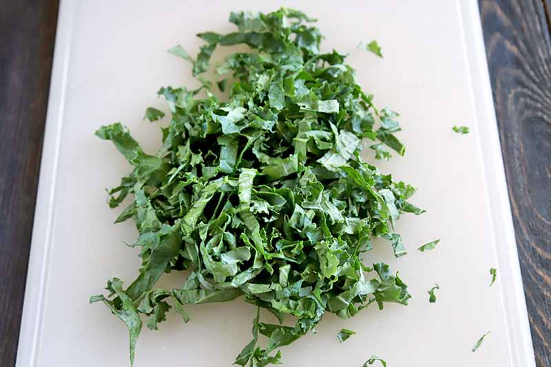 Horizontal image of a pile of thinly chopped green kale on a white cutting board, on a dark gray surface.