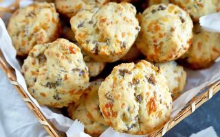 Horizontal closely cropped oblique overhead image of a basket lined with parchment paper and filled with sausage cheese biscuits, on a blue-gray surface topped partially with more paper.