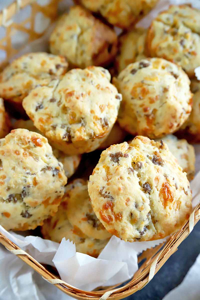 Closely cropped vertical overhead image of a basked lined with white parchment paper and filled with homemade sausage and cheddar cheese biscuits, on a gray surface with a white cloth and more paper.