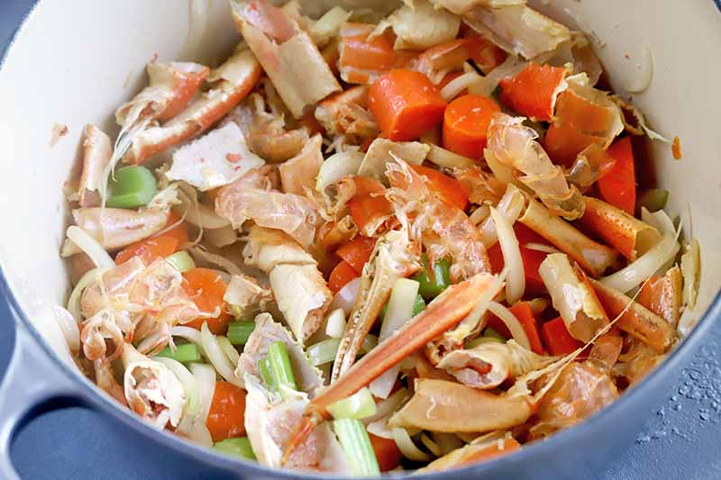 Horizontal image of cut vegetables and crab legs in a pot.