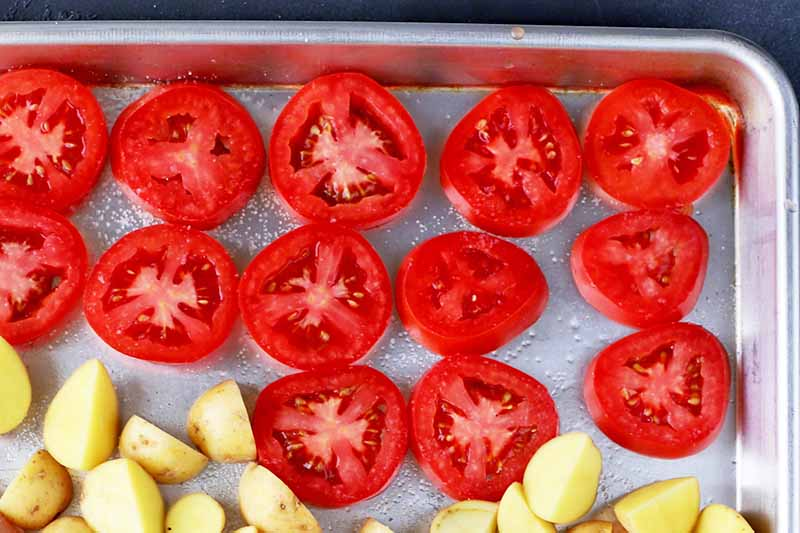 Horizontal overhead image of sliced plum tomatoes arranged in a single layer on a metal rimmed baking sheet with cut potatoes.