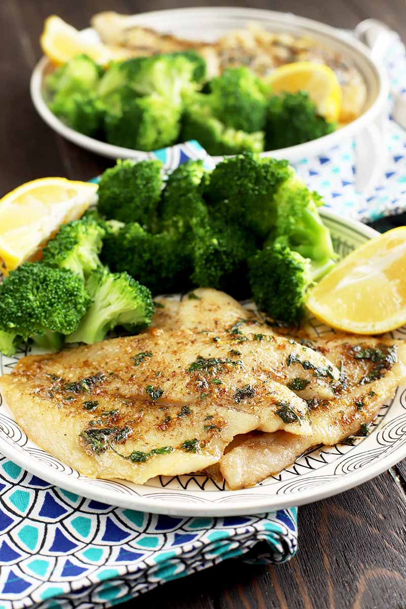 Vertical image of two plates with seasoned sole, broccoli florets, and lemon wedges on a blue napkin.
