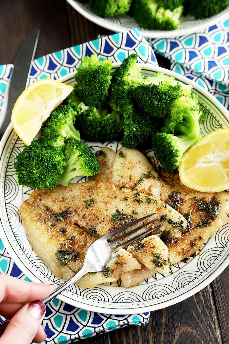 Vertical top-down image of a fork taking a piece of seasoned fish on a plate with broccoli and lemon wedges.