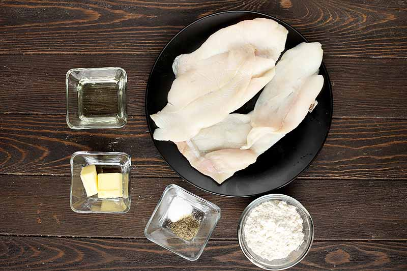 Horizontal image of uncooked fish fillets on a black plate next to seasonings in glass bowls.