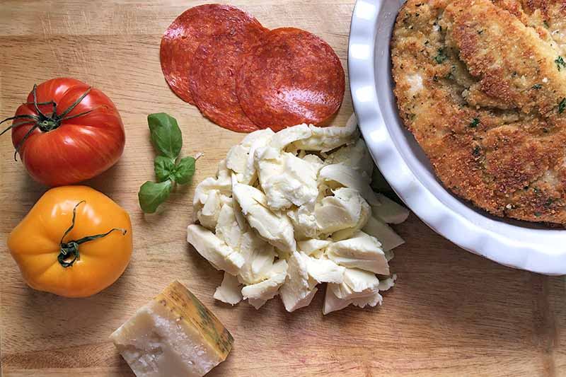 Horizontal overhead image of one red and one yellow tomato, several leaves of basil, chopped fresh mozzarella, a wedge of Parmigiano-Reggiano, a few slices of pepperoni, and a white pie plate of chicken cutlets, on a wood surface.