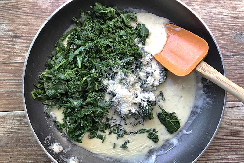Overhead horizontal image of collard greens, grated cheese, and cream sauce in a nonstick frying pan, being stirred by an orange rubber spatula with a wooden handle, on a light brown unfinished wood surface.