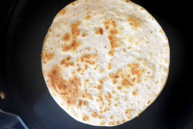 Horizontal overhead image of a browned flour tortilla in a large nonstick skillet.