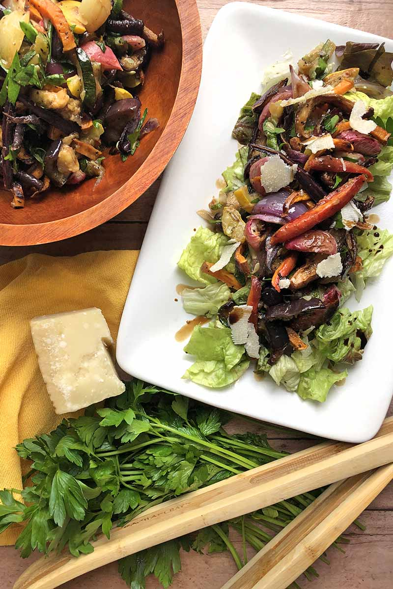 Vertical overhead image of a white platter and a wooden serving bowl of roasted vegetable salad, on a wood surface with wooden tongs, a sprig of fresh flat-leaf Italian parsley, and a block of Parmesan cheese.