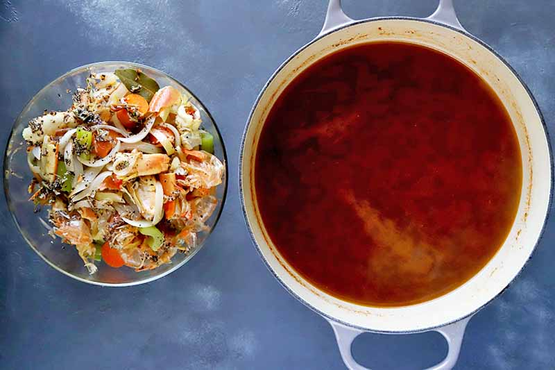 Horizontal image of a bowl of vegetables, aromatics, and seafood scraps next to a pot of a dark red broth.