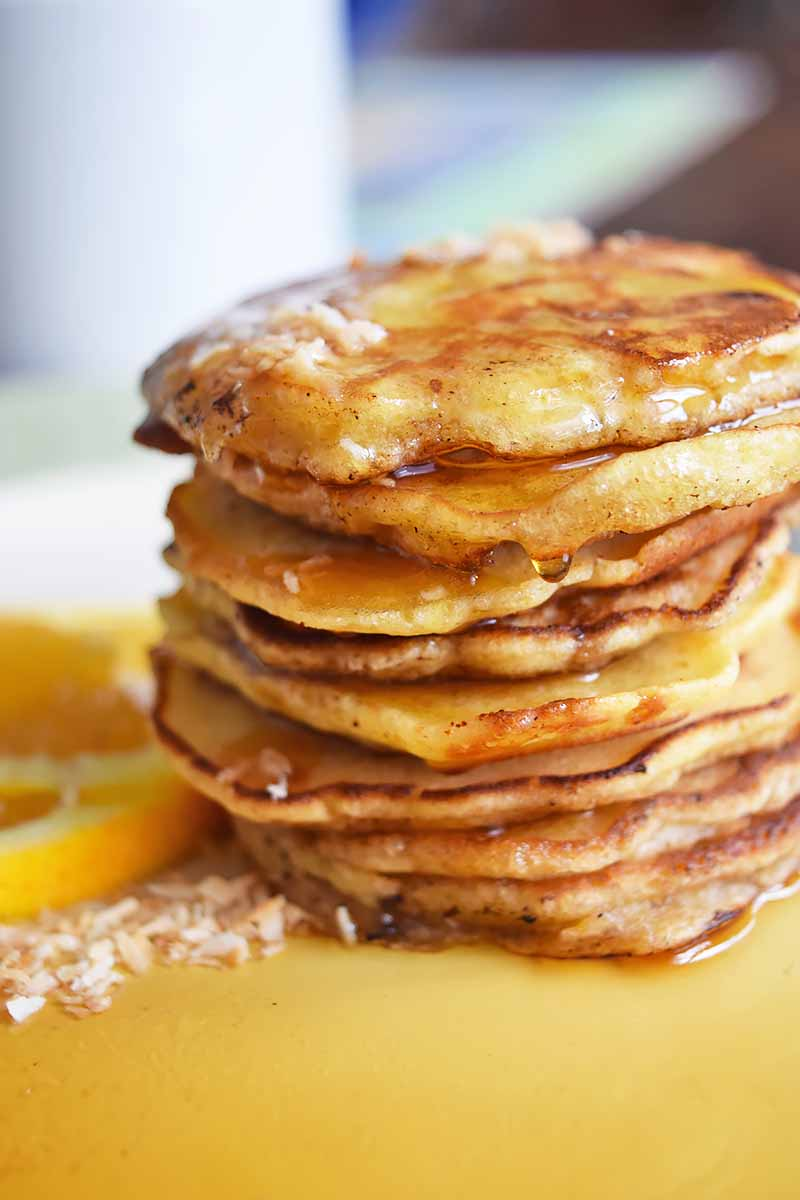 Vertical image of a tall stack of pancakes covered in syrup next to oranges.