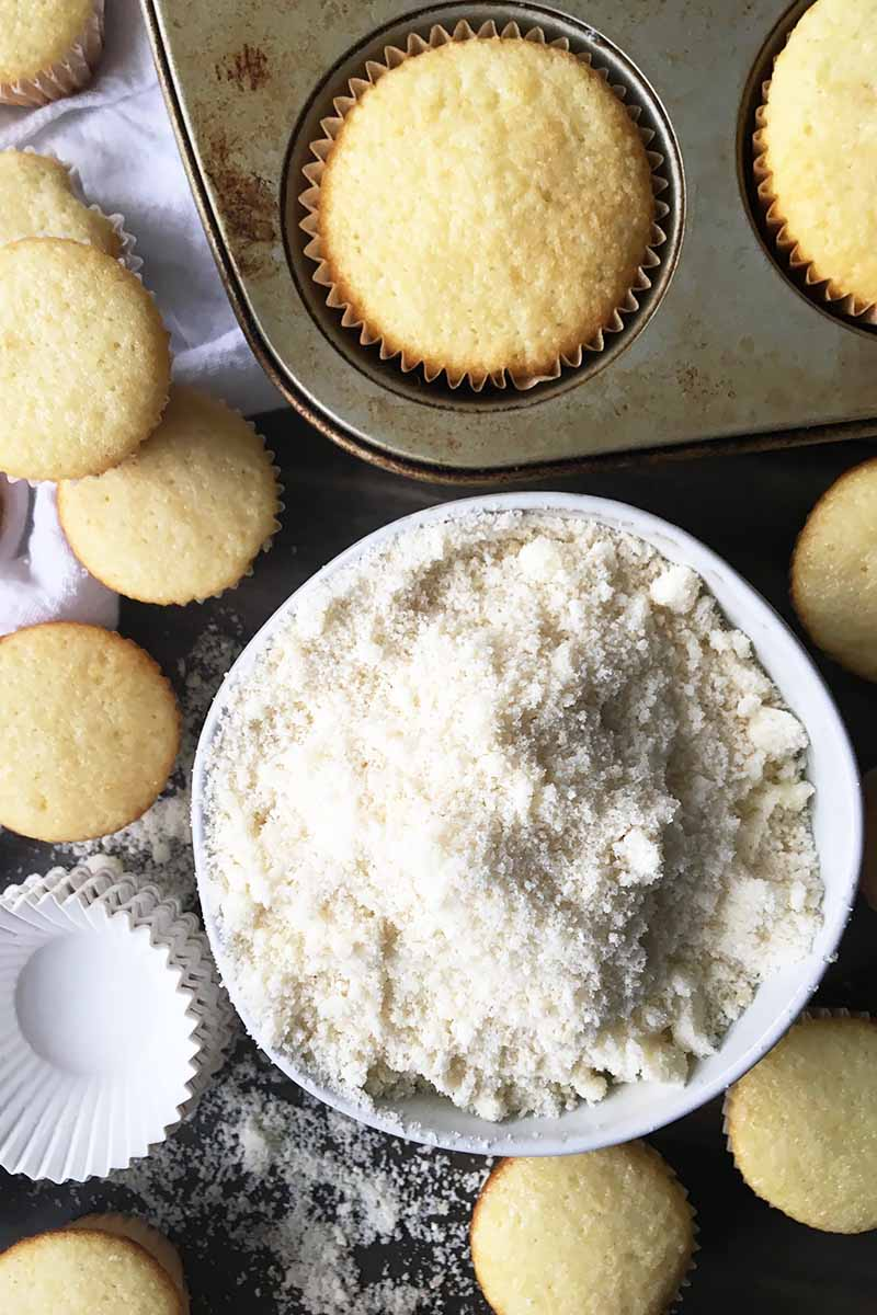 Vertical top-down image of a dry white powder in a dish next to baked yellow cupcakes and liners.